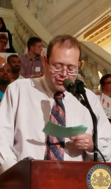 A person with short brown hair wearing glasses, and a shirt and tie speaking into a microphone at a rally.