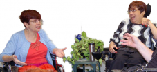 Two people talking, both using wheelchairs. One with short red hair, glasses, a red shirt and skirt and light blue jacket, the other with short dark brown hair, glasses, black pants and a black, gray and white striped sweater.