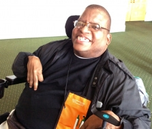 A smiling person with dark hair, wearing glasses and black clothes, using a wheelchair.