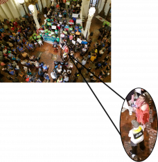 A person in a peach dress and another person in a gray hat and white shirt in a small photo with arrows pointing to where they are standing in a larger photo of over 1000 people at a rally at the Pennsylvania Capitol.