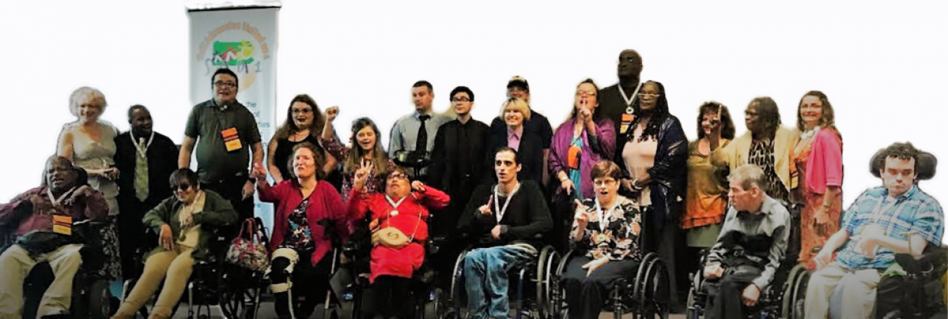 Twenty three smiling people holding up one finger to show they are united as one. Some of them are standing, some using wheelchairs.