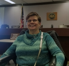 A smiling person with short brown hair, wearing glasses and a green sweater, using a wheelchair, in front of a sign for the Pennsylvania Independent Regulatory Review Commission.